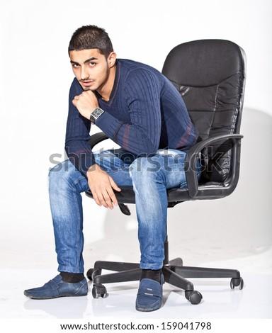 Handsome arab businessman sitting on chair - stock photo