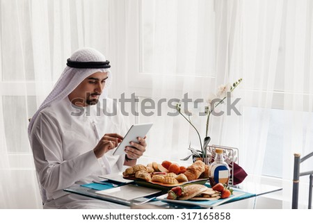 Handsome Arabian Male Using Digital Tablet During Breakfast - stock photo