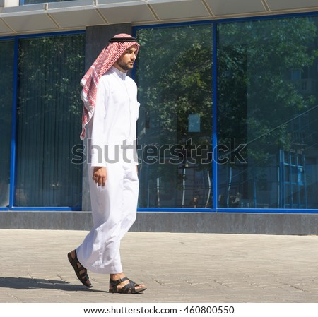 Handsome arabian man walking along the street