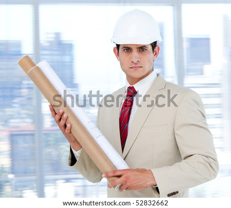 Handsome architect holding a blueprint  in the company