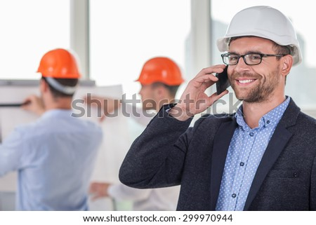 Handsome architect is talking on the phone with his customer. He is smiling with happiness. There is his construction team on the background. Their plan of building was approved - stock photo
