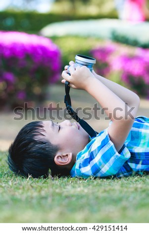 Handsome asian boy taking photo by vintage film camera, exploring nature at park, on summer in the day time. Child in nature, outdoors portrait. Active lifestyle, curiosity, pursuing a hobby concept. - stock photo