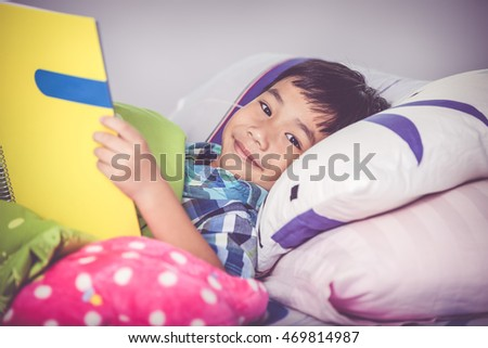Handsome asian child smiling and lying down on bed in bedroom. Children study at home, education concept. Boy looking at camera and he has a look of enjoyment on his face. Vintage tone effect.