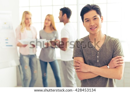 Handsome Asian guy is looking at camera and smiling, in the background his colleagues are discussing business affairs - stock photo