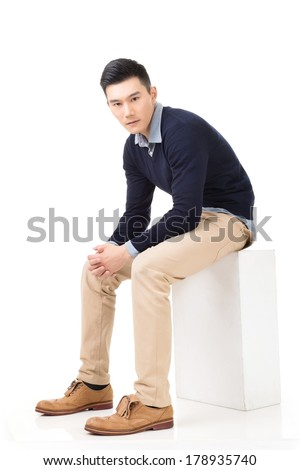 Handsome Asian guy sit pose, full length portrait isolated on white background.