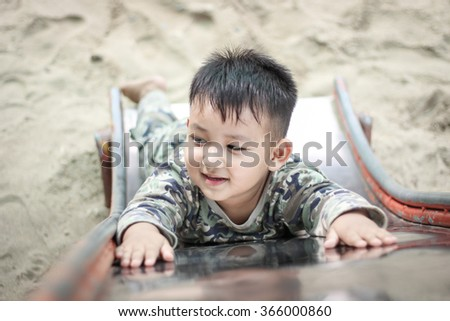 Handsome asian kid having fun playing slider at outdoor playground on a bright sunny day. Little boy in green soldier shirt. - stock photo