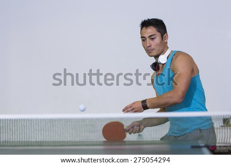 Handsome asian man about to return a shot during a game of table tennis, space for text or graphics - stock photo