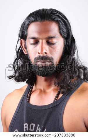 Handsome Asian man in meditation, against white background.