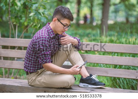 Handsome Asian man is sitting on the park bench and immersed in using his smartphone