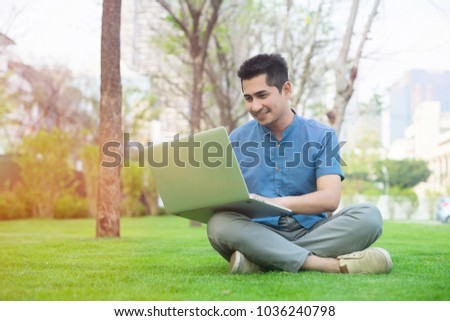 Handsome asian man using laptop in the garden or in the park happily.