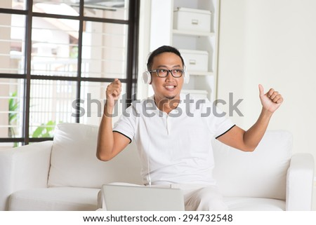 Handsome Asian man using tablet computer. Smiling Southeast Asian college student relaxing and listening to music at home. Asian model.