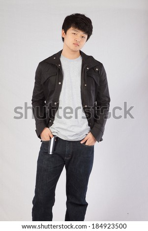 Handsome Asian teenager standing with his hands in his pockets and looking at the camera with a thoughtful expression  - stock photo