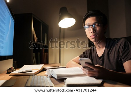 Handsome asian young man in glasses studying and using smartphone in the evening at home - stock photo