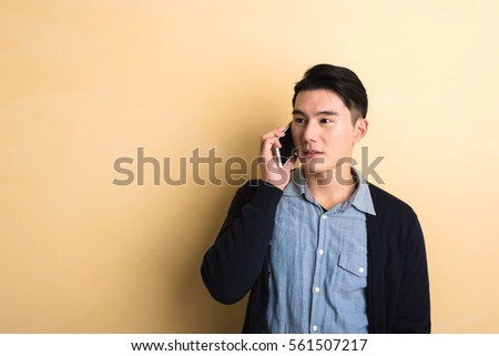 handsome Asian young man talk on phone, shot at studio yellow background