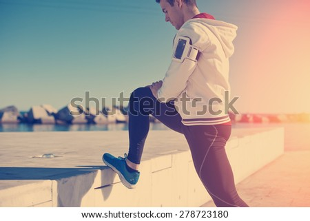 Handsome athlete doing legs stretching exercise after workout outdoors near the sea (intentional sun glare and vintage color) - stock photo