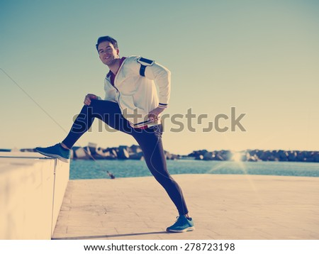 Handsome athlete doing stretching exercise after workout outdoors (intentional vintage color)
