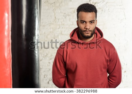 Handsome athlete in maroon jumper is standing in a gym beside red and black punching bags, holding the hands backwards and thinking of the fight strategy, looking into the camera. - stock photo