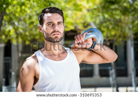 Handsome athlete outfit with a kettlebell on a sunny day