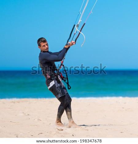 handsome athlete prepares his kite for kitesurfing training - stock photo
