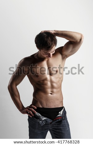 Handsome athletic man looking at side in unbuttoned jeans. Strong bodybuilder with six pack,perfect abs, shoulders, biceps, triceps and chest. Great fitness body. Ideal for commercial. Gray background - stock photo