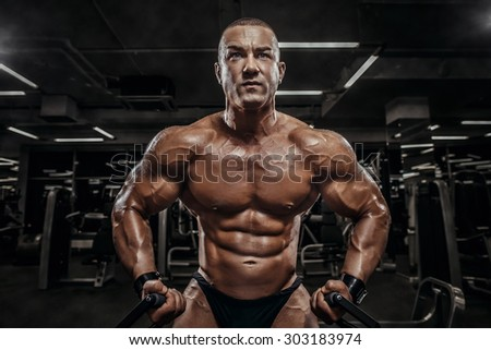 Handsome athletic man power training with dumbbells pumping muscle. Strong bodybuilder six pack, perfect ABS, shoulders, biceps, triceps and chest. Young adult bodybuilder doing weight lifting in gym. - stock photo