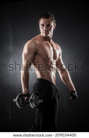 Handsome athletic man pumping up muscles with dumbbells - stock photo