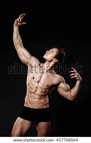 Handsome athletic man. Strong bodybuilder with six pack, perfect abs, shoulders, biceps, triceps and chest. Great fitness body. Ideal for commercial  - stock photo