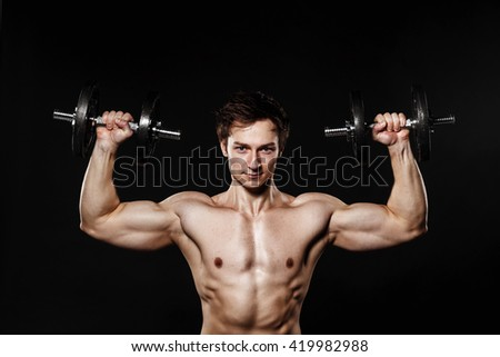 Handsome athletic man with dumbbells confidently looking forward. Strong bodybuilder with six pack, perfect abs, shoulders, biceps, triceps and chest. Great fitness body. Ideal for commercial  - stock photo
