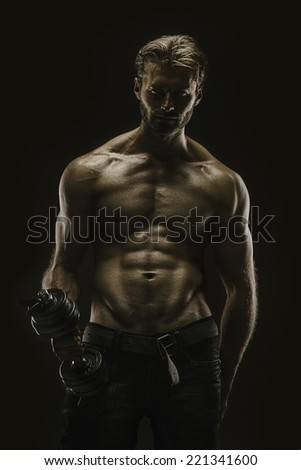 Handsome athletic young aesthetic man isolated on black - stock photo