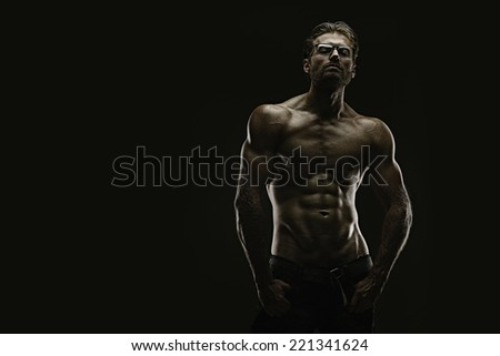 Handsome athletic young aesthetic man isolated on black