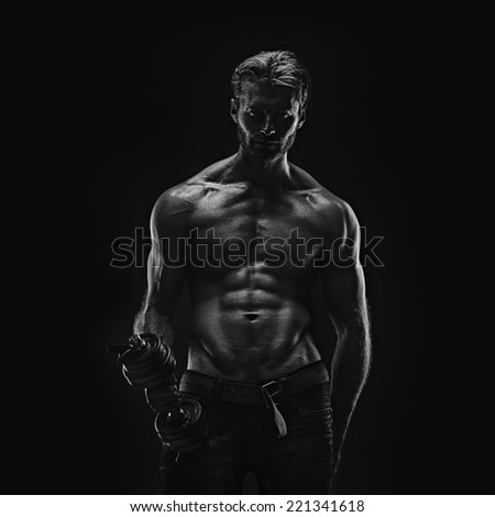 Handsome athletic young aesthetic man isolated on black. Black and white - stock photo