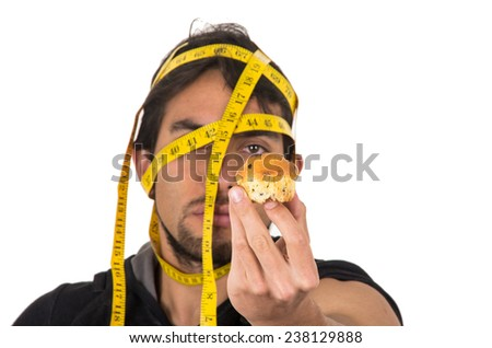 handsome athletic young man wrapped around measuring tape holding muffin concept of diet isolated on white - stock photo