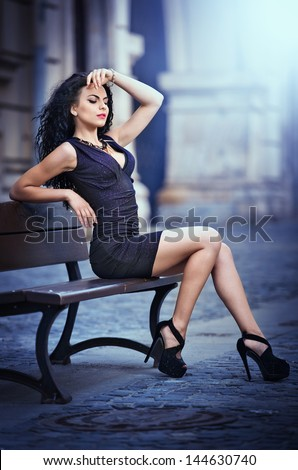 handsome attractive girl wearing short skirt and high heels standing outside in urban scene.Fashion model in blue short skirt with long sexy legs on the street .Woman sitting on bench in the city - stock photo