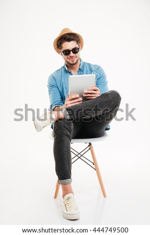 Handsome attractive happy joyful young man using tablet and sitting on the chair isolated on the white background - stock photo