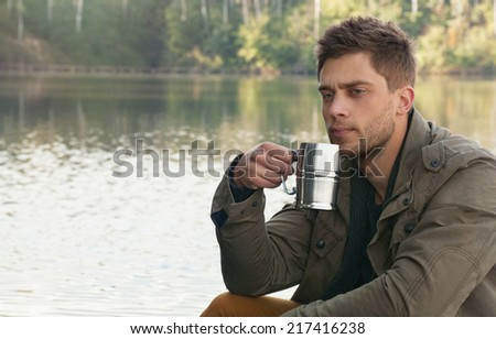 handsome attractive man at the lake on beautiful nature background, relax concept - stock photo