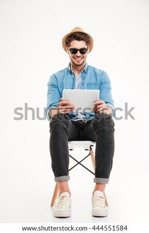 Handsome attractive smiling happy young male using tablet and sitting on the chair isolated on the white background - stock photo