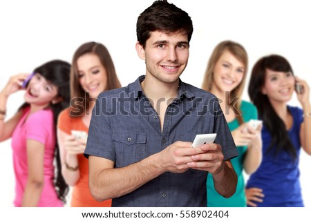 handsome attractive young man using mobile phone. four diverse ethnicity woman at the background