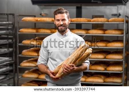 Handsome baker in uniform holding baguettes with bread shelves on the background at the manufacturing - stock photo