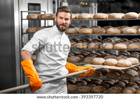 Handsome baker in uniform with orange working gloves putting with shovel from the oven bread loafs on the shelves at the manufacturing - stock photo
