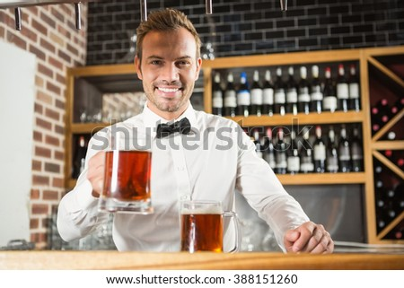 Handsome bar tender holding a pint in a pub - stock photo