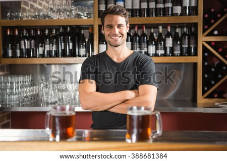 Handsome bar tender standing behind his counter in a pub - stock photo