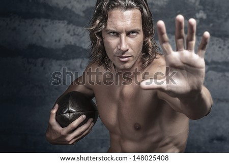 handsome bare chested muscle model is opening his hand in halt gesture and holds football ball - stock photo