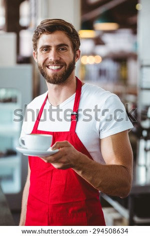 Handsome barista holding a cup of coffee at the cafe