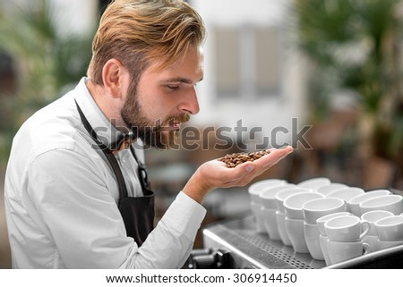 Handsome barista in classical uniform checking coffee beans at the cafe terrace - stock photo
