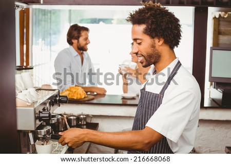 Handsome barista making a cup of coffee at the coffee shop - stock photo