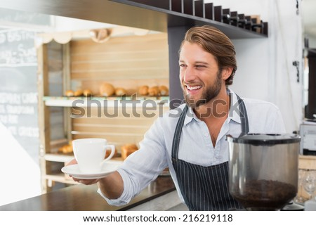Handsome barista offering a cup of coffee at the coffee shop - stock photo