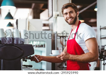 Handsome barista preparing a cup of coffee with the coffee machine - stock photo