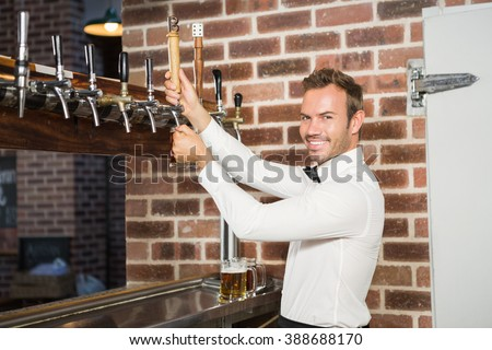 Handsome barman pouring a pint of beer in a pub - stock photo