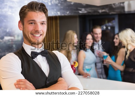 Handsome barman smiling at camera at the bar - stock photo