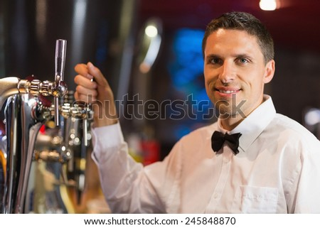 Handsome barman smiling at camera in a bar - stock photo